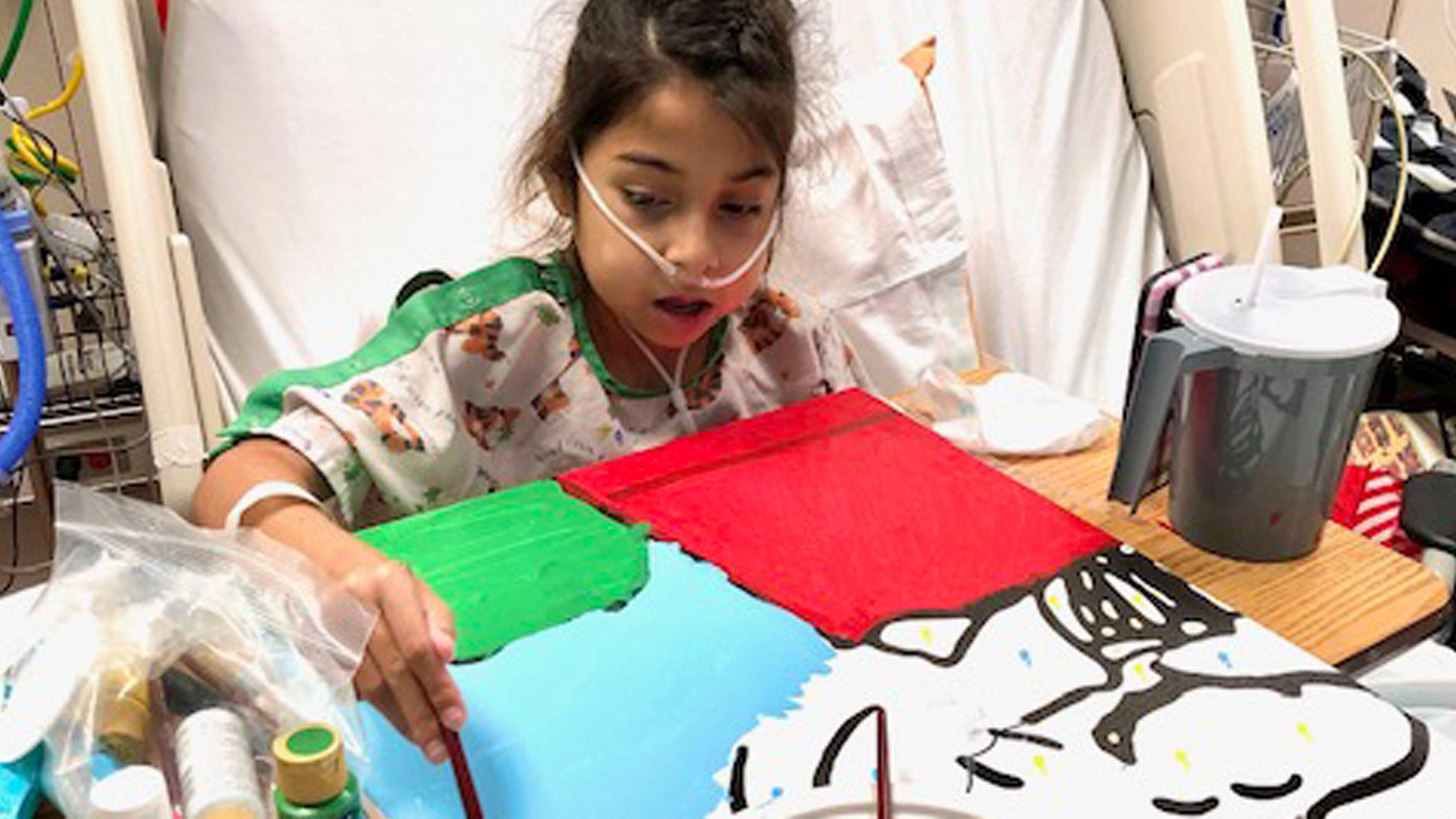 A little girl, in a hospital bed, paints part of a mural at a hospital.