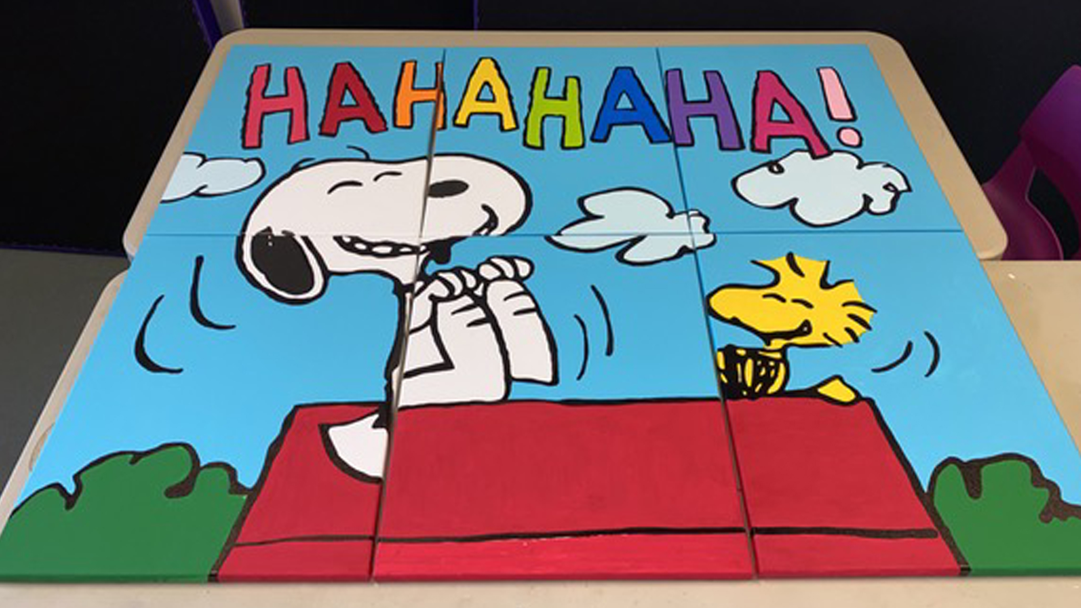 A painted mural of a black and white beagle and yellow bird laughing.