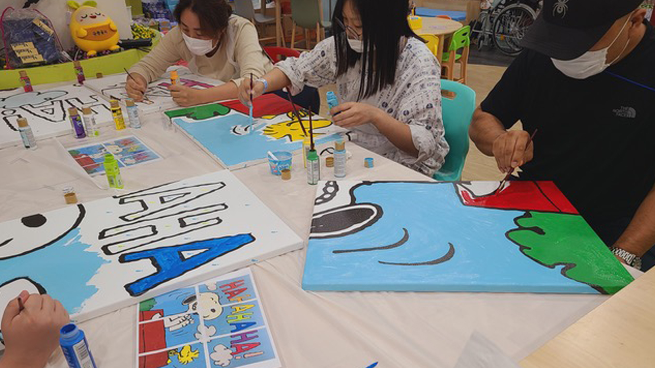 Children sitting at a table and painting a mural in a hospital.