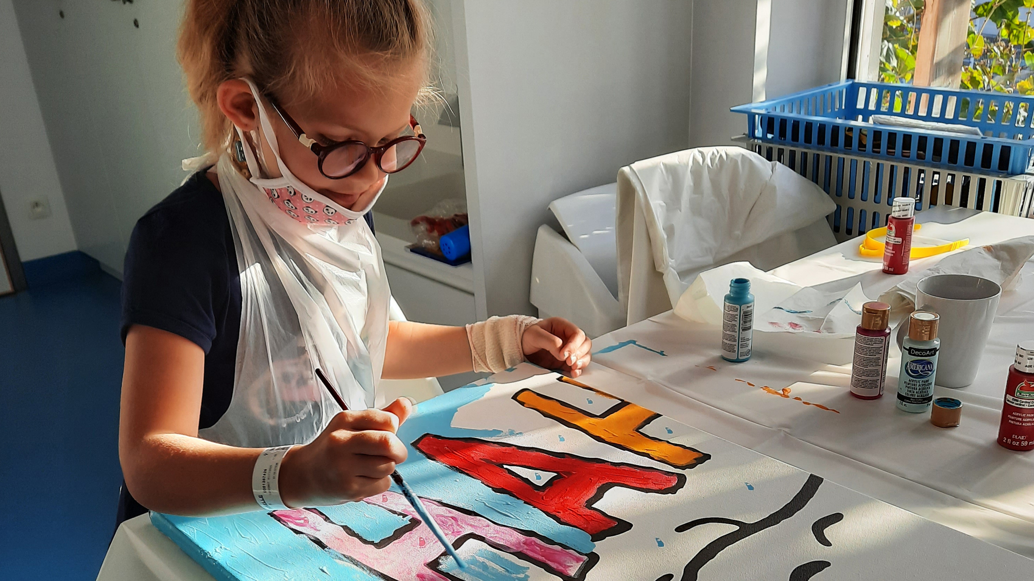 A little girl wearing a face mask is sitting at a table and painting.