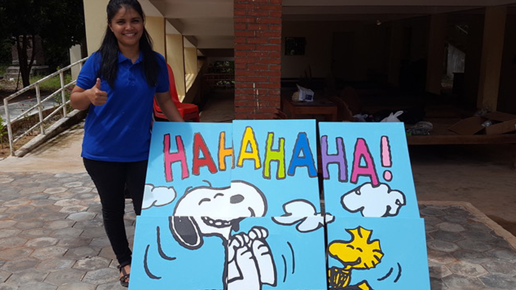 An adult woman standing next to a painted mural of a black and white beagle and yellow bird laughing