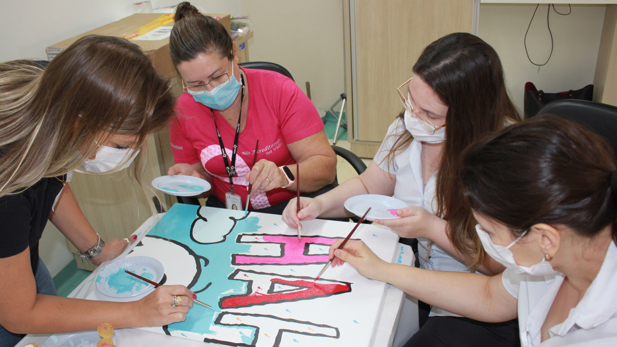 Adult women painting a mural at a hospital in Brazil