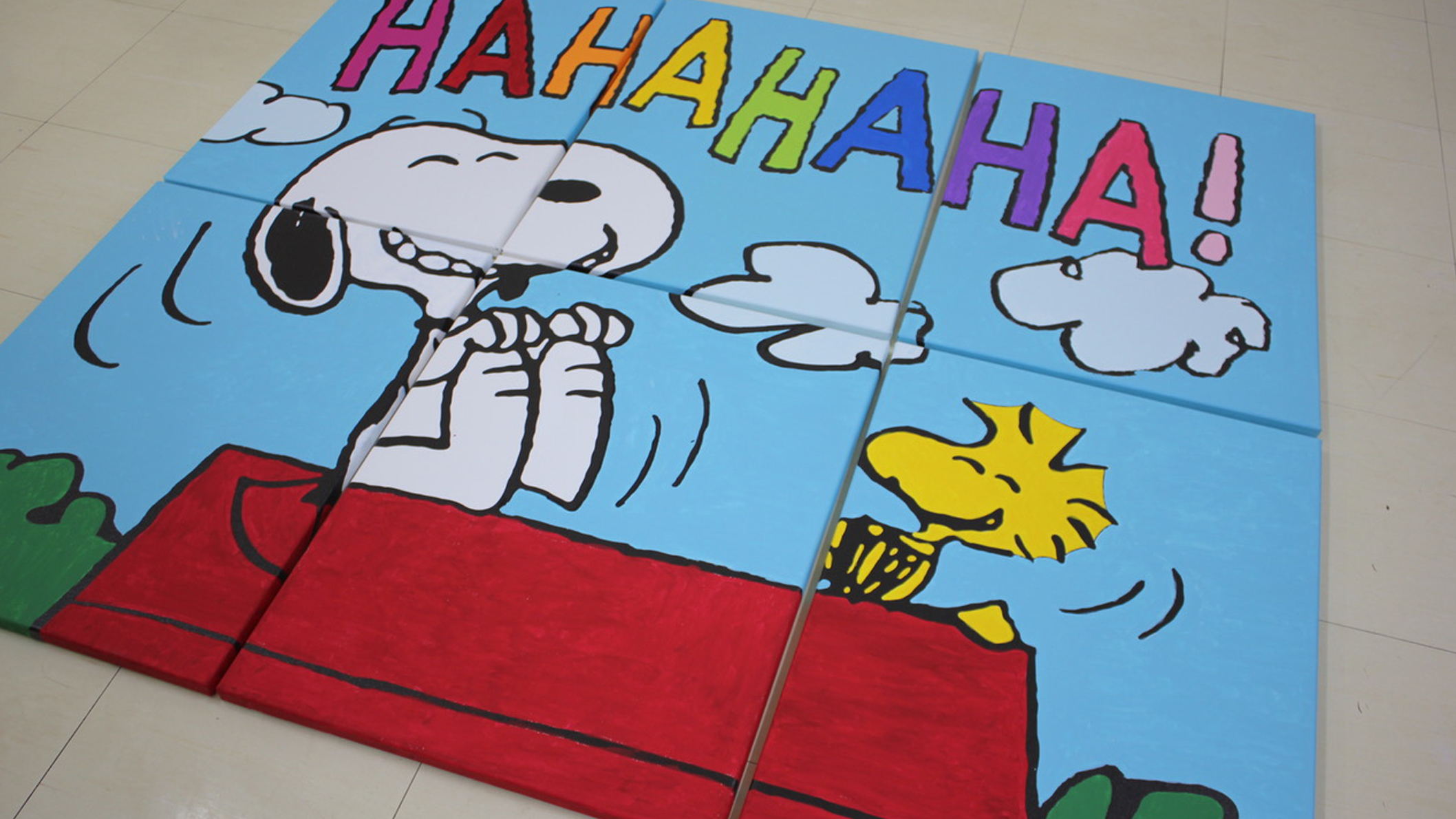 A painted mural of a black and white beagle and yellow bird laughing