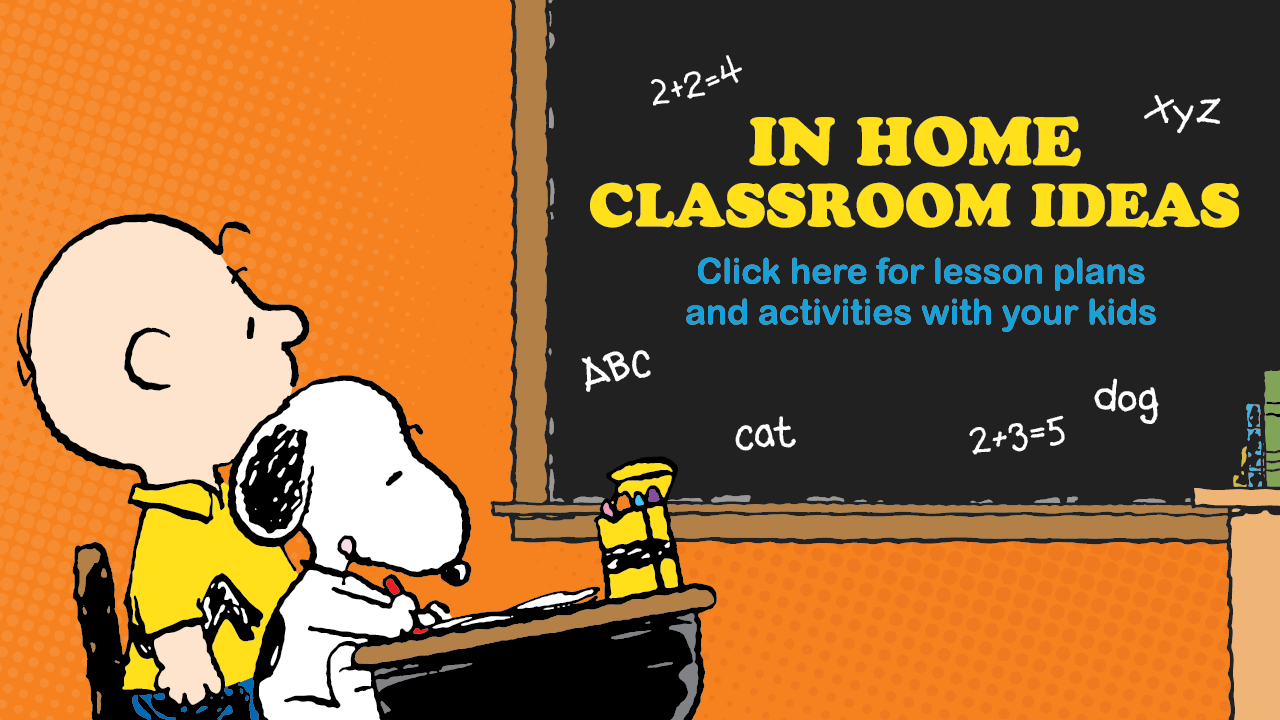 A boy in a yellow shirt and a white dog sitting at a desk in front of a black chalkboard.