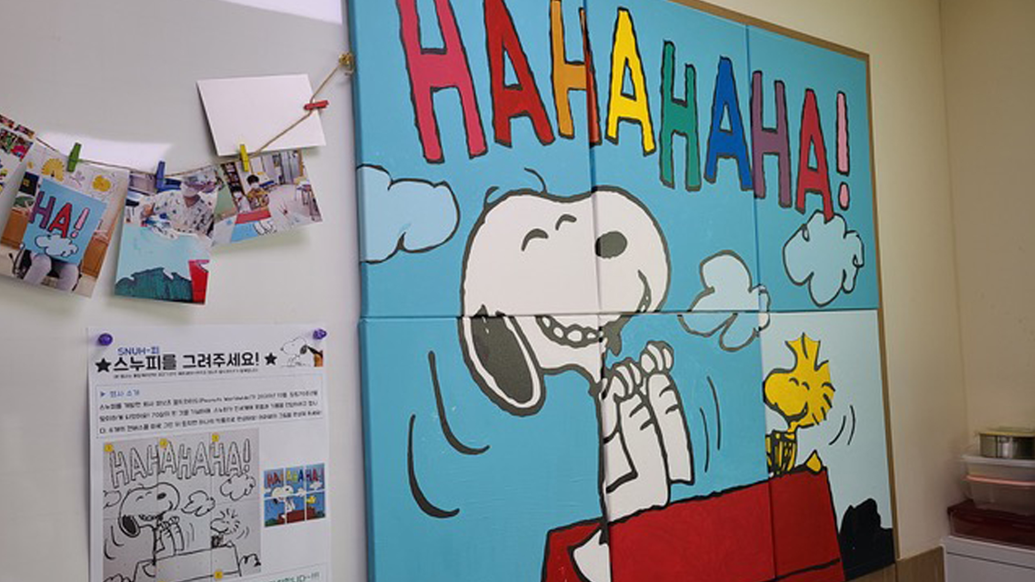 A painted mural of a black and white beagle and yellow bird laughing hanging on a wall