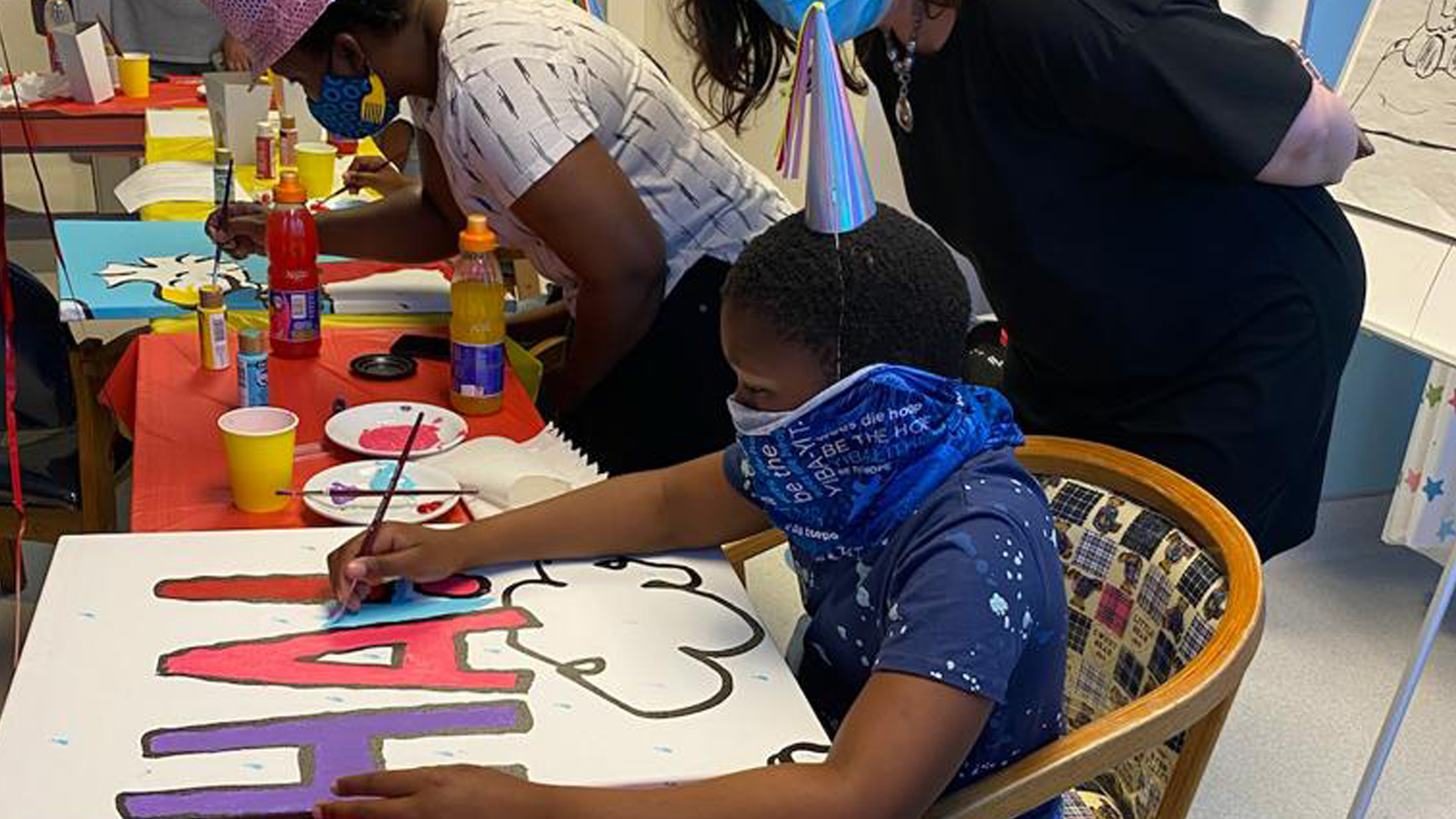 Little boy wearing a facemask is sitting at a table and painting a mural.